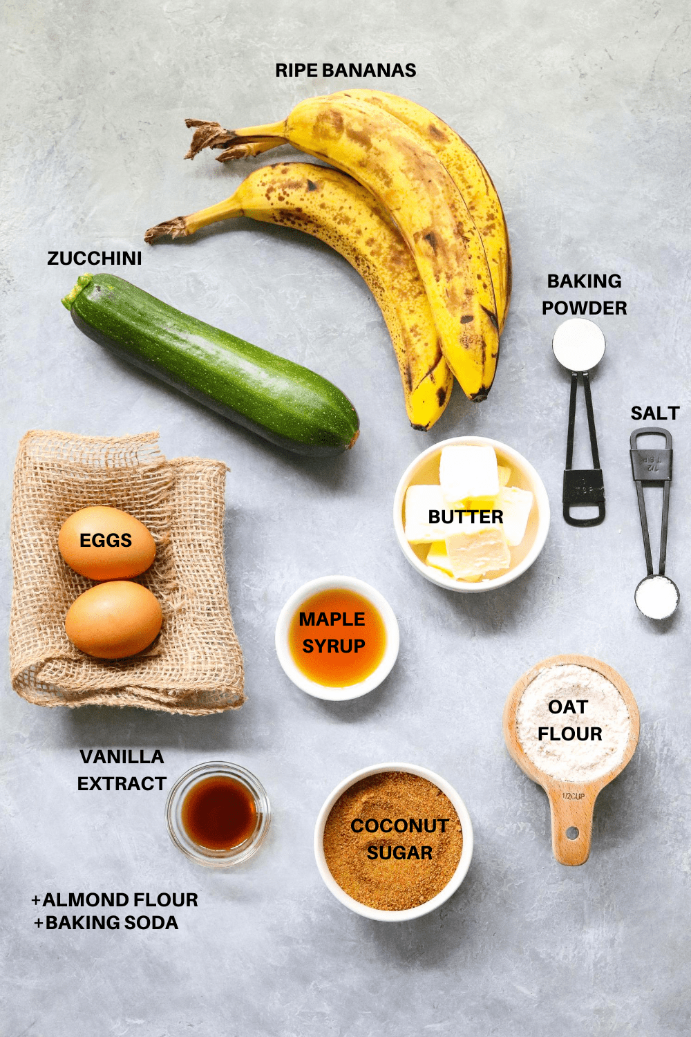 Ripe bananas, zucchini, butter, eggs and flour on a gray board