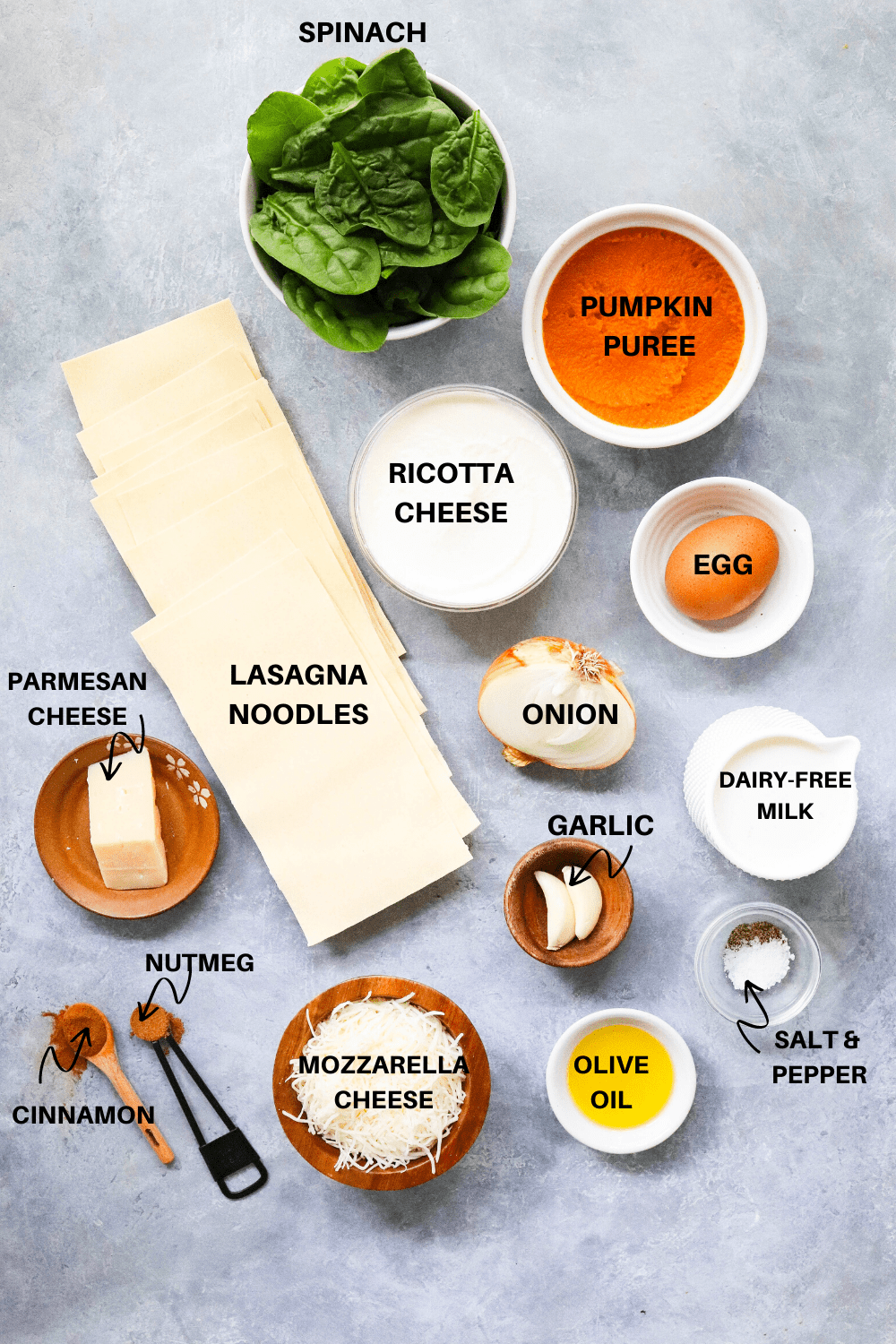 spinach, pumpkin, lasagna noodles, ricotta cheese, egg and onion on a gray board
