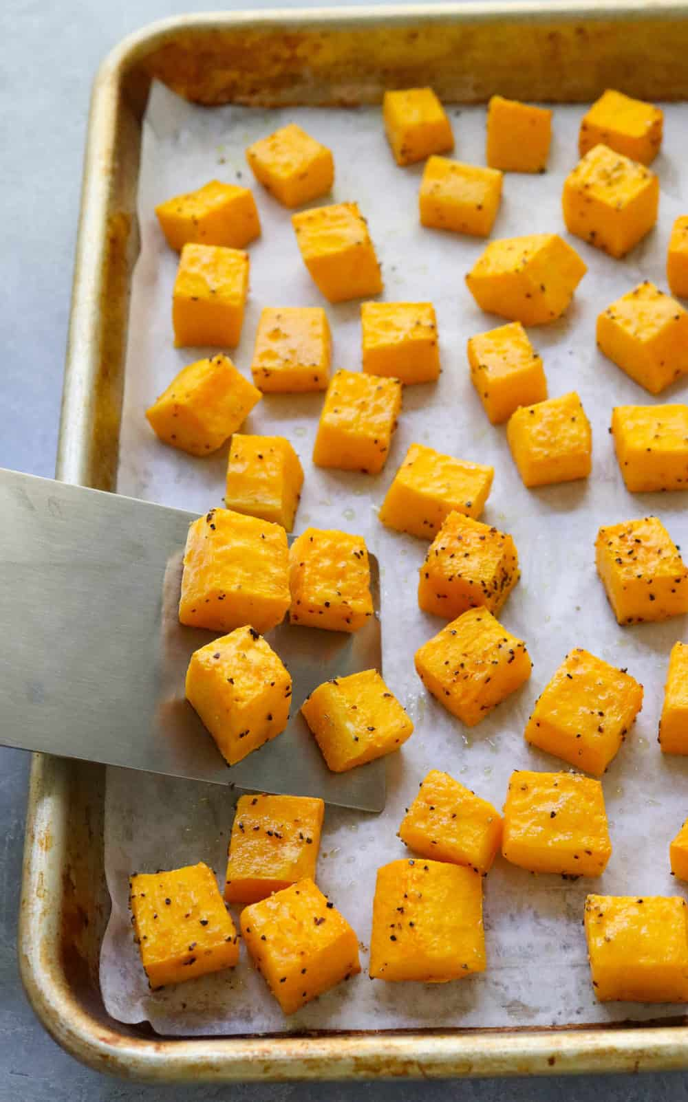 cubed butternut squash on a pan with a spatula picking up the squash