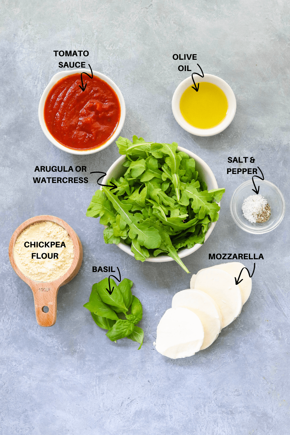 tomato sauce, greens, flour, oil, salt and pepper on a gray board