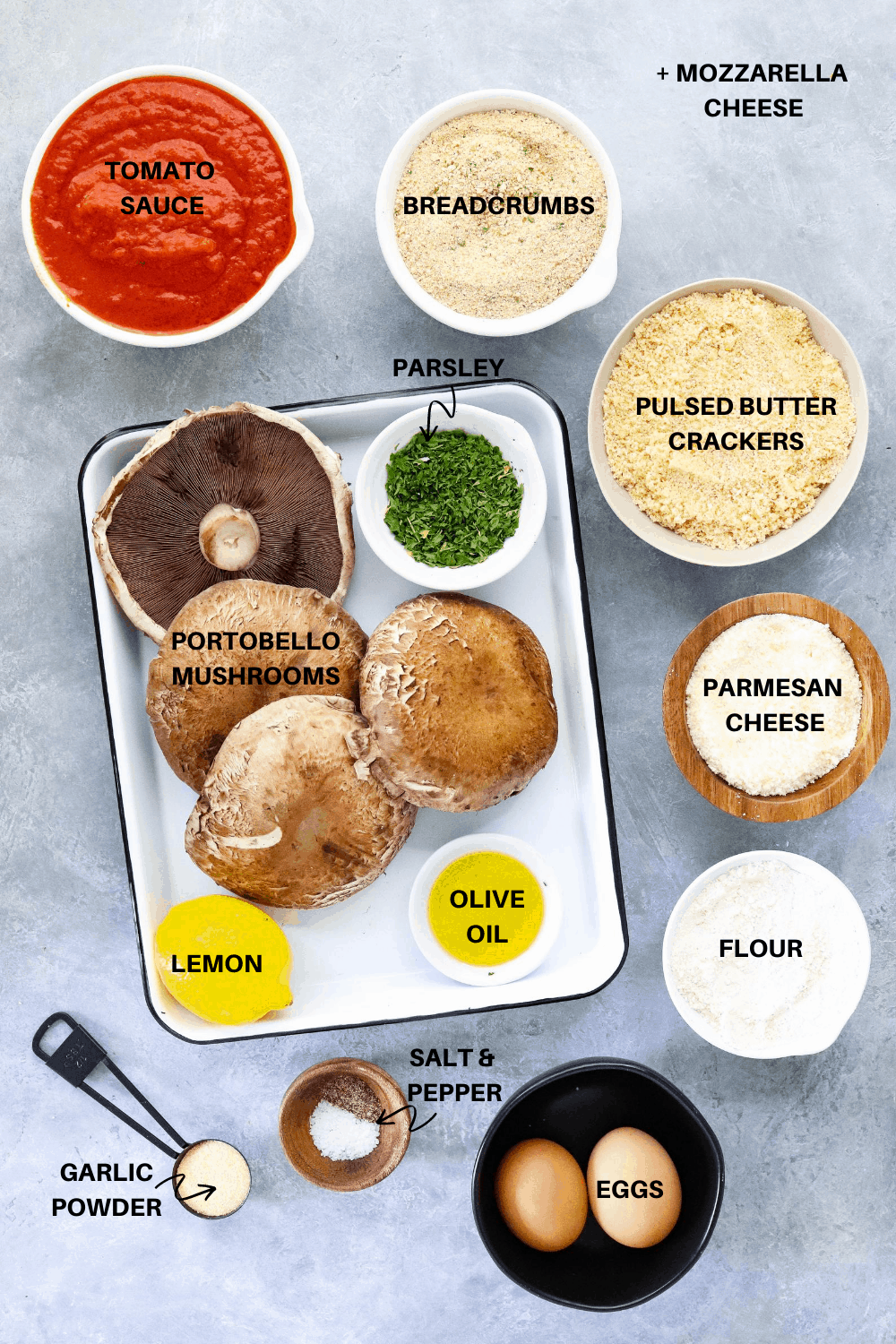 Mushrooms, red sauce, parmesan, breadcrumbs and spices on a gray board