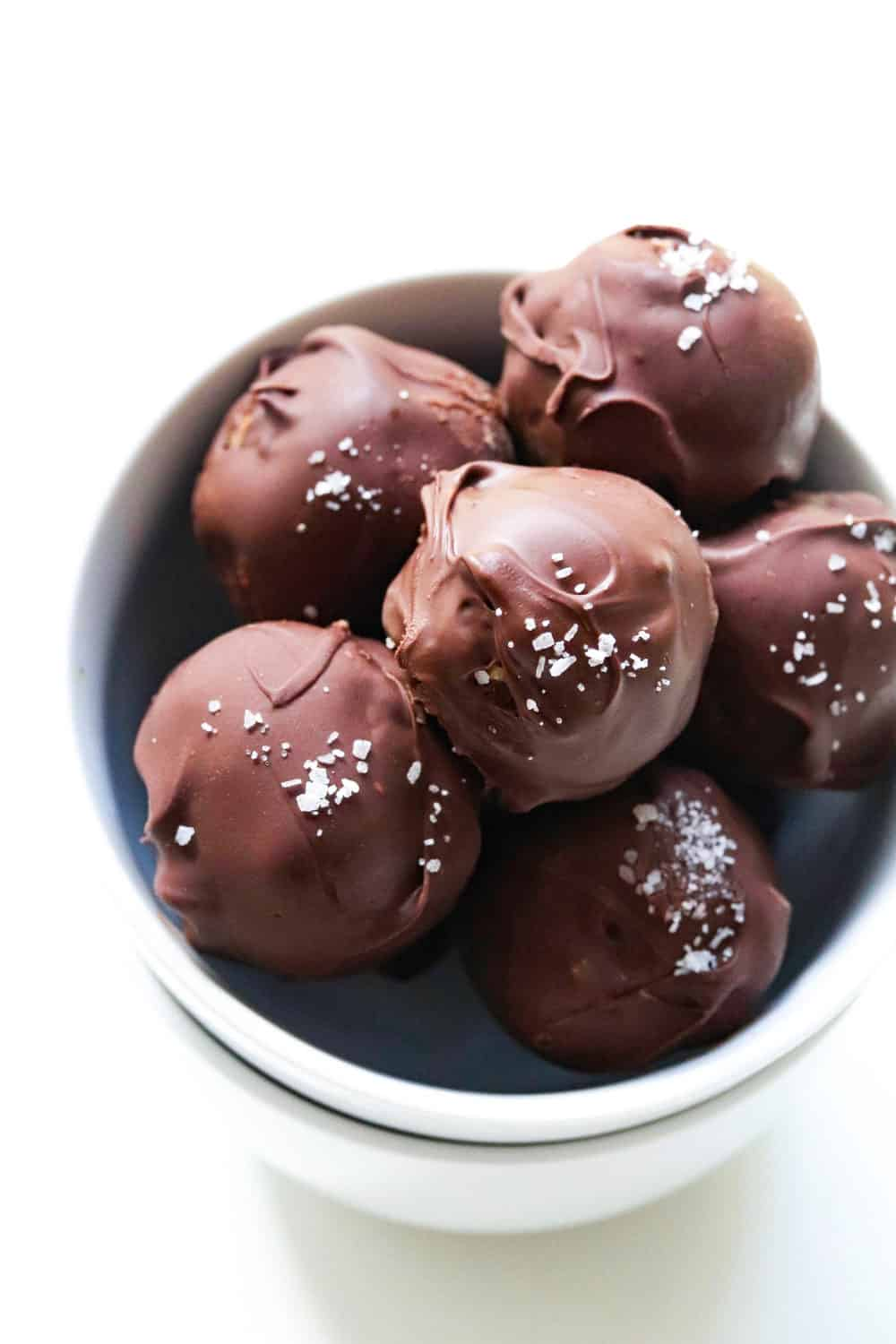 Chocolate energy balls in a round white bowl with sea salt on top