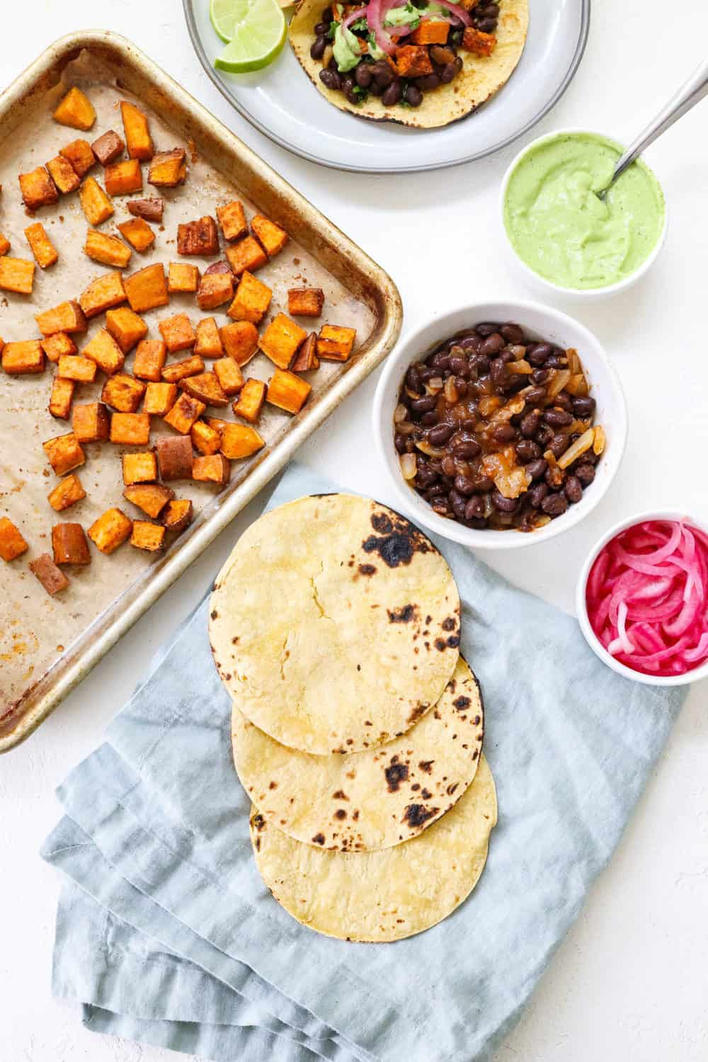 sweet potatoes, black beans, avocado sauce and tortillas on a white board