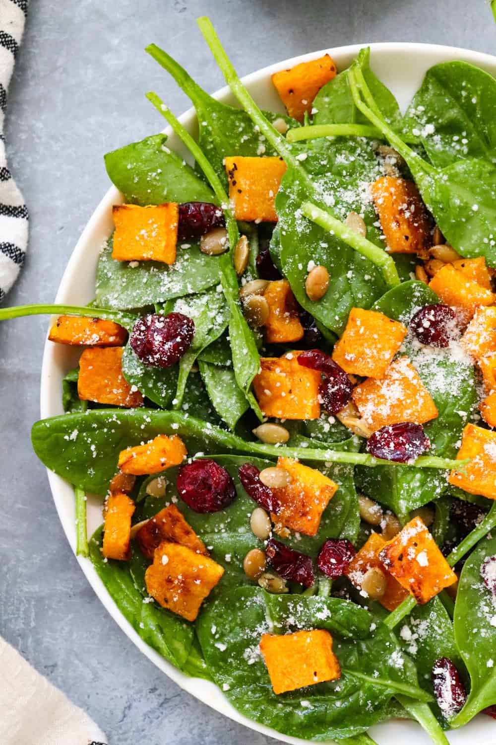 cubed roasted butternut squash on spinach salad with parmesan cheese and cranberries on it