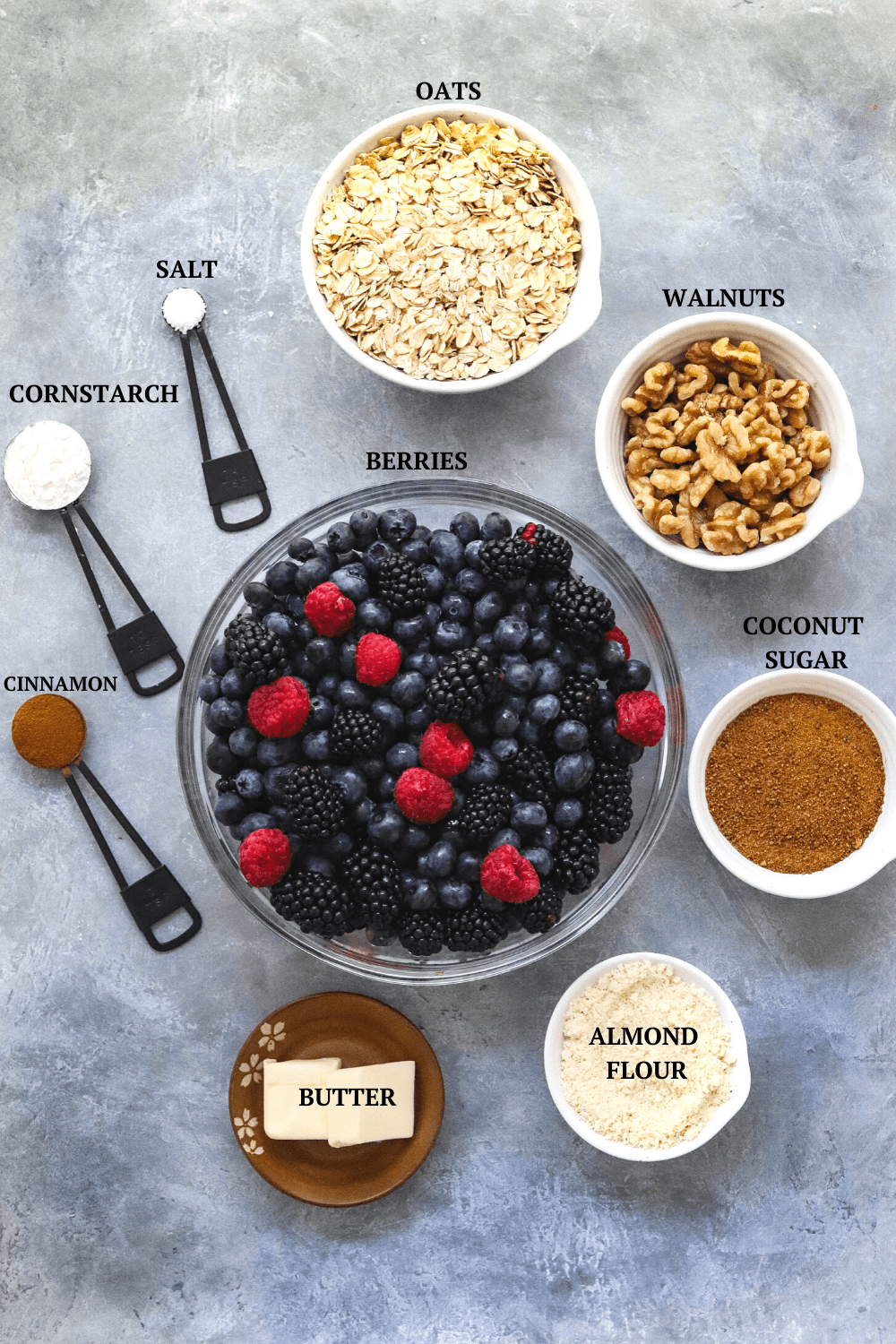 berry crips ingredients : berries, oats, flour, butter on gray board