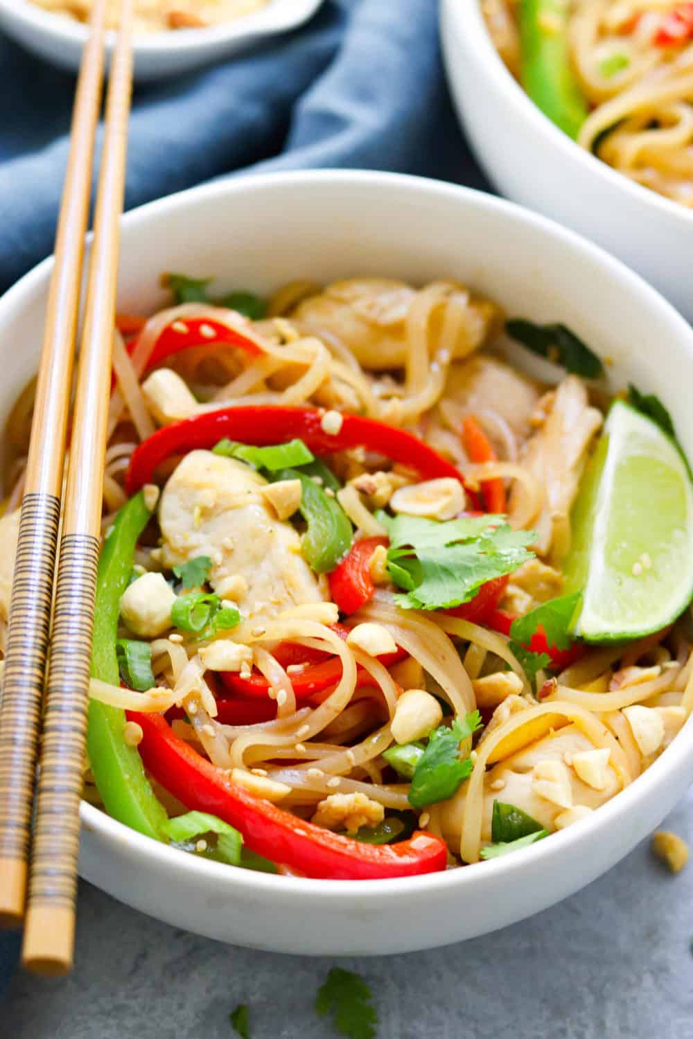 chicken pad thai with bell peppers in a white bowl with a pair of chopsticks on top of the bowl
