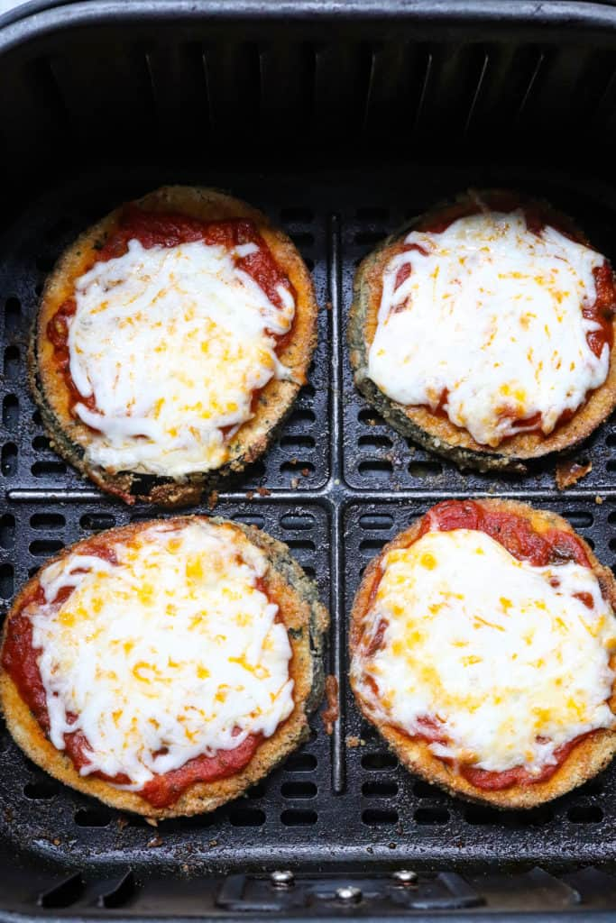 4 slices of fried eggplant with tomato sauce and melted cheese on top of it in a black air fryer basket