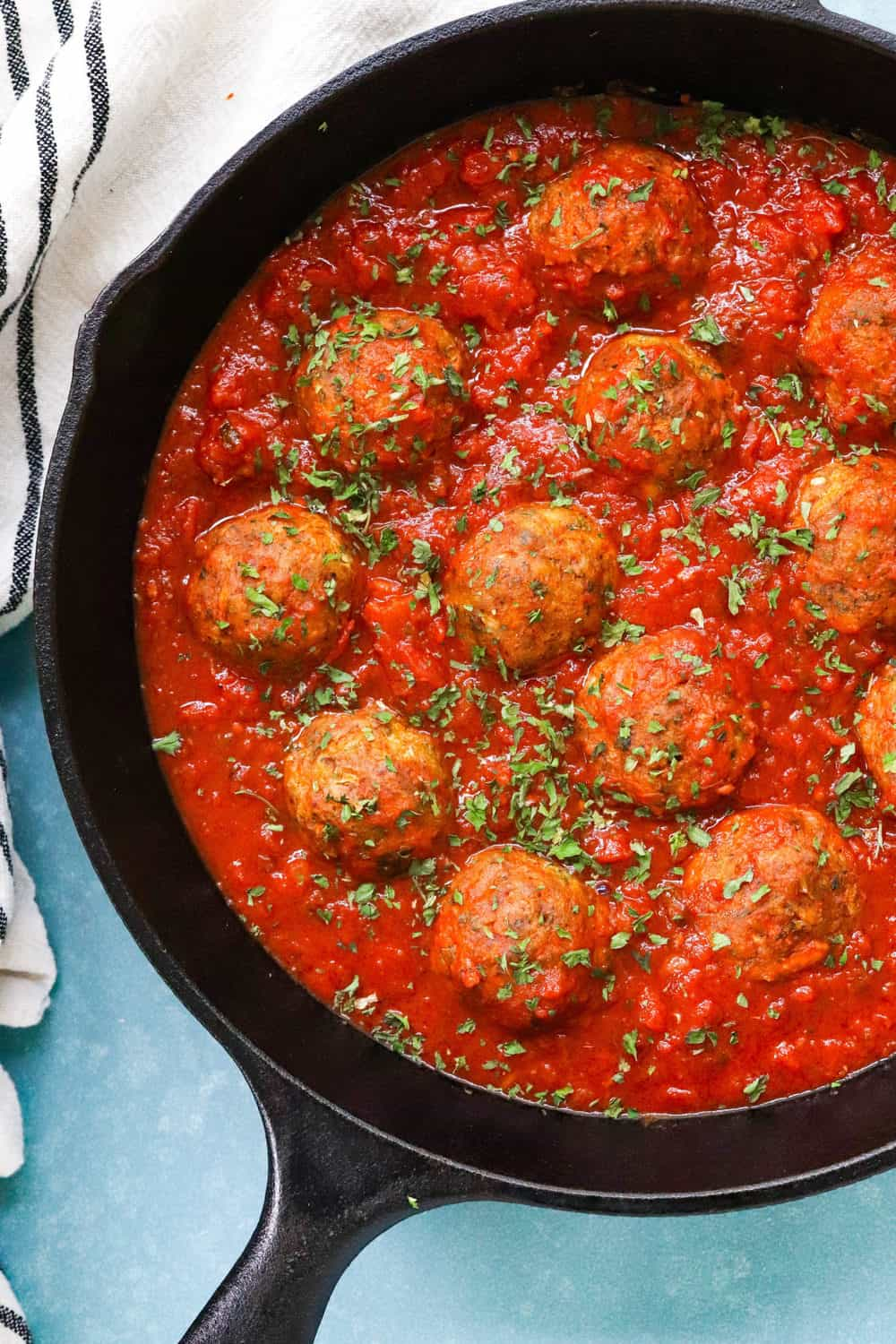 vegan meatballs in red tomato sauce in a cast iron pan on a blue board