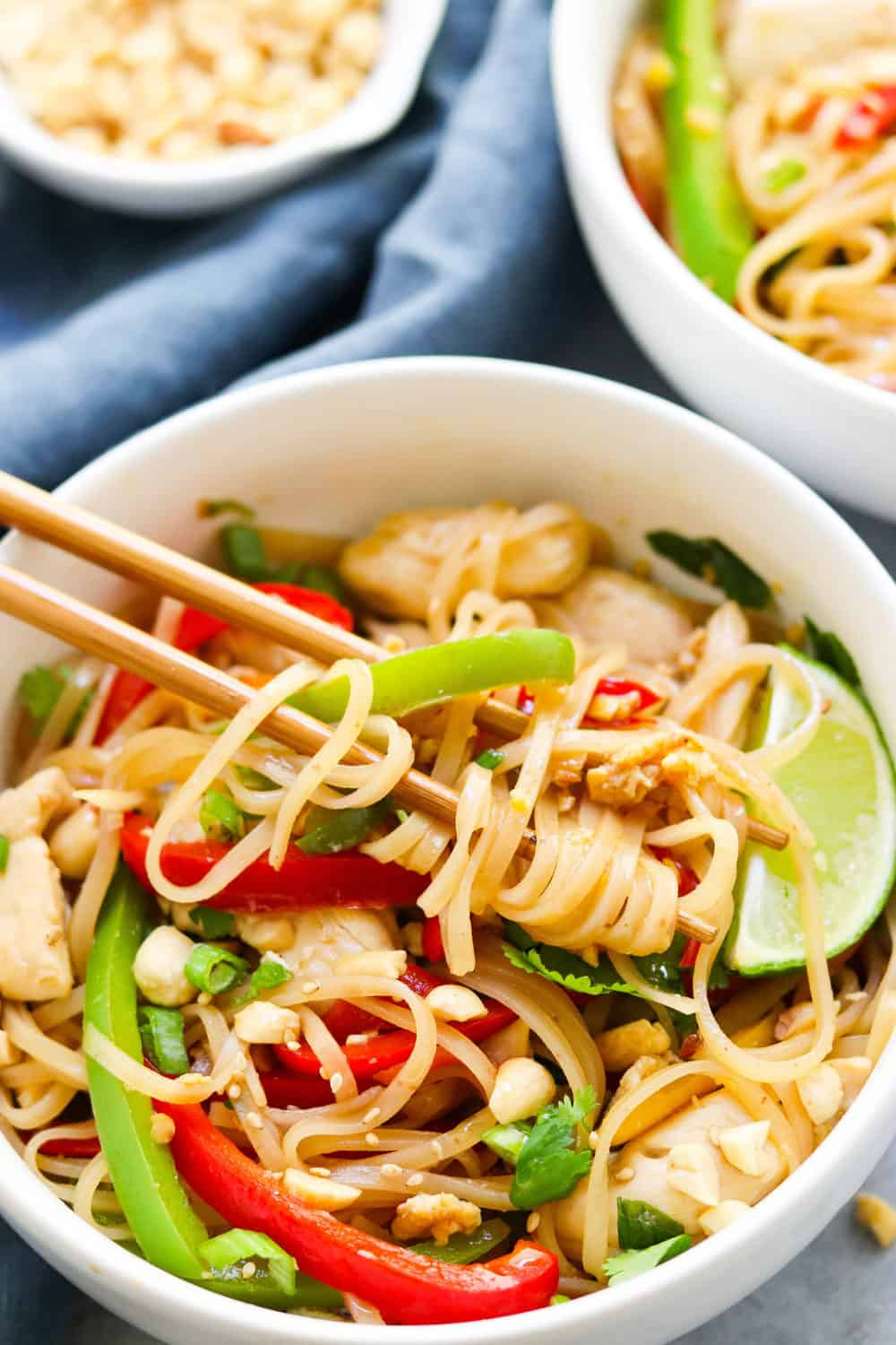 noodles with chicken and veggies covered in pad thai sauce with chopsticks in it.