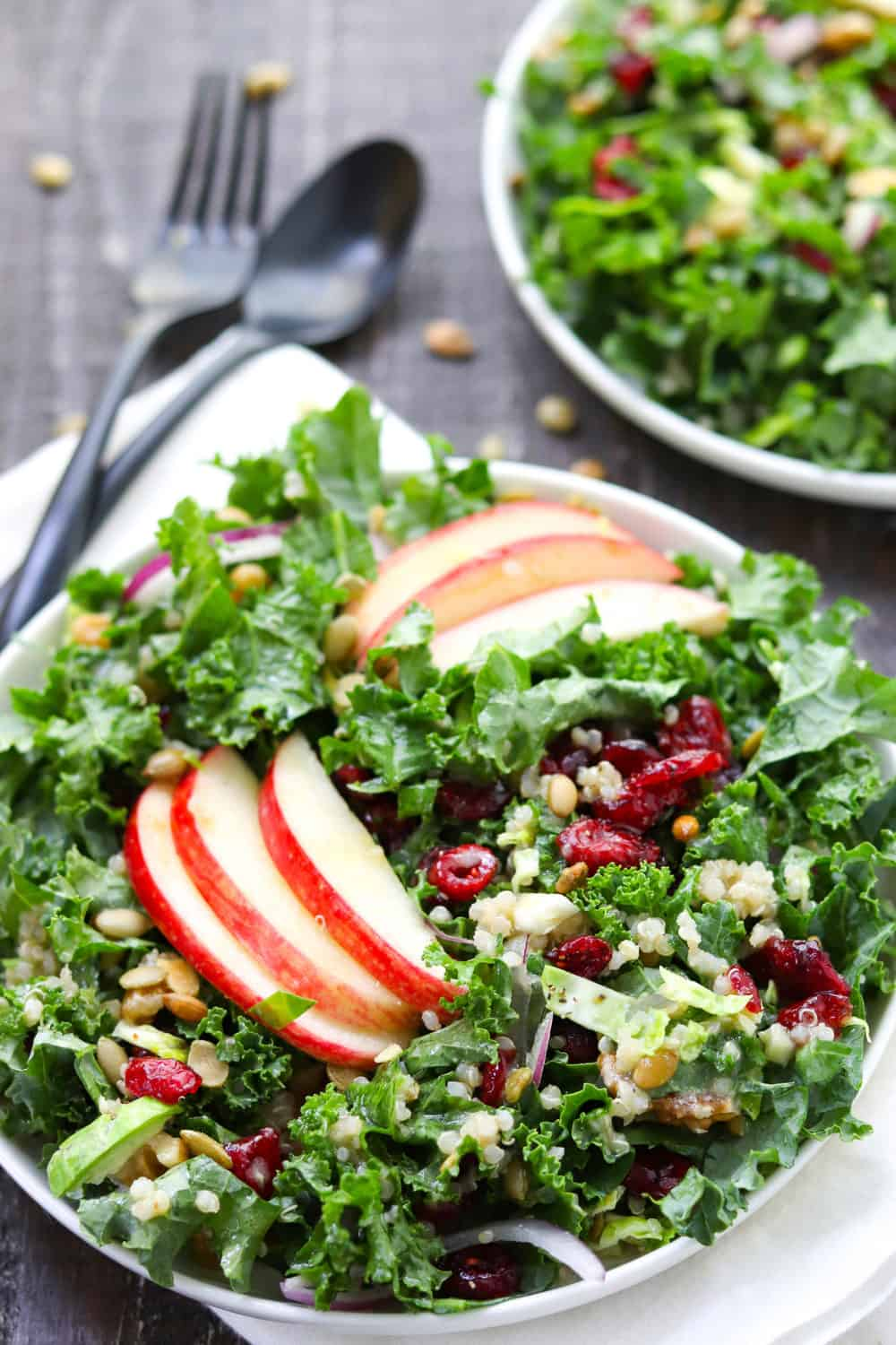 chopped kale salad with apples and onions mixed together on a white round plate with silverware next to it.