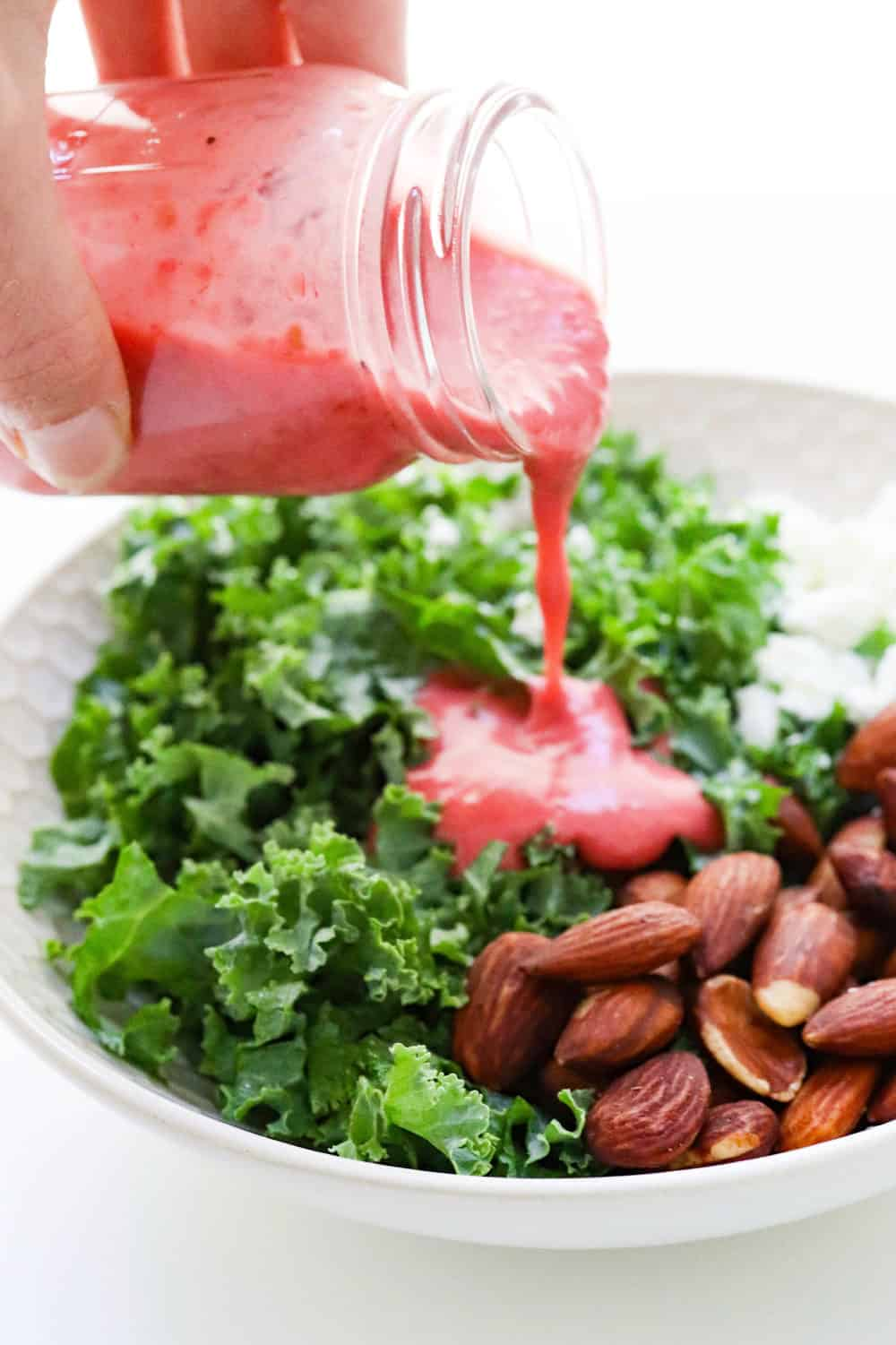 pouring healthy raspberry salad dressing onto kale salad