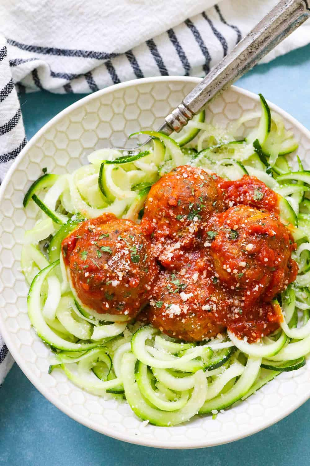veggie meatballs on a bed of spiraled zucchini with red sauce on top