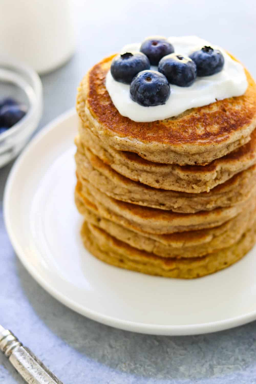 large stack of fluffy almond flour pancakes with whipped cream and a few blueberries on top of the pancakes