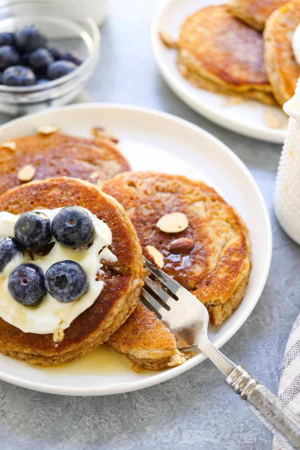 3 almond flour pancakes on a round white plate with yogurt and berries on top of it with a fork cutting into one of the pancakes