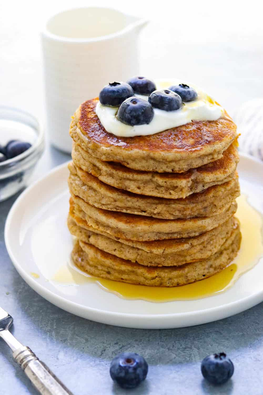 pile of pancakes with blueberries and cream with more blueberries behind it.