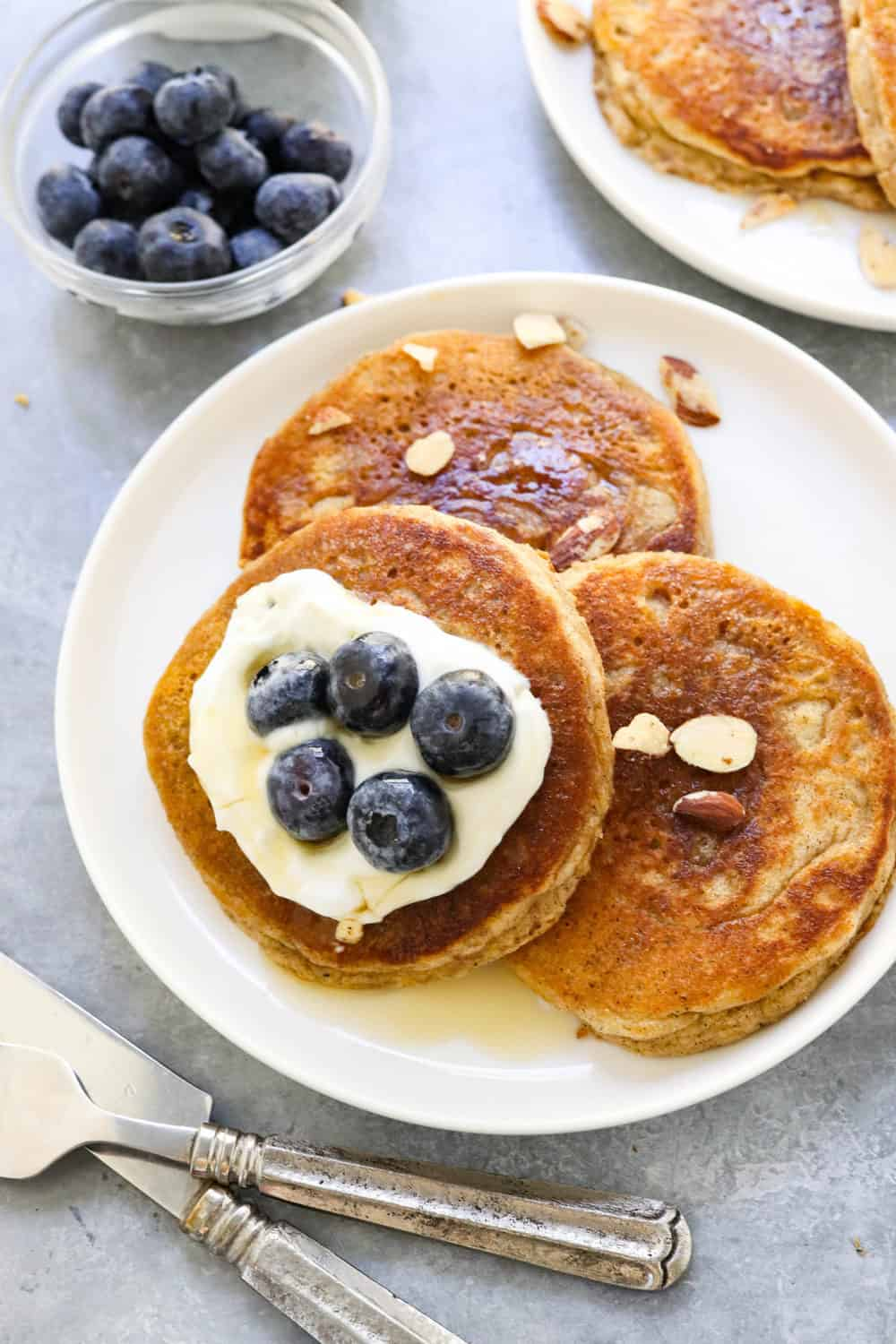 round plate of pancakes with syrup and blueberries on top of them and silverware next to it.