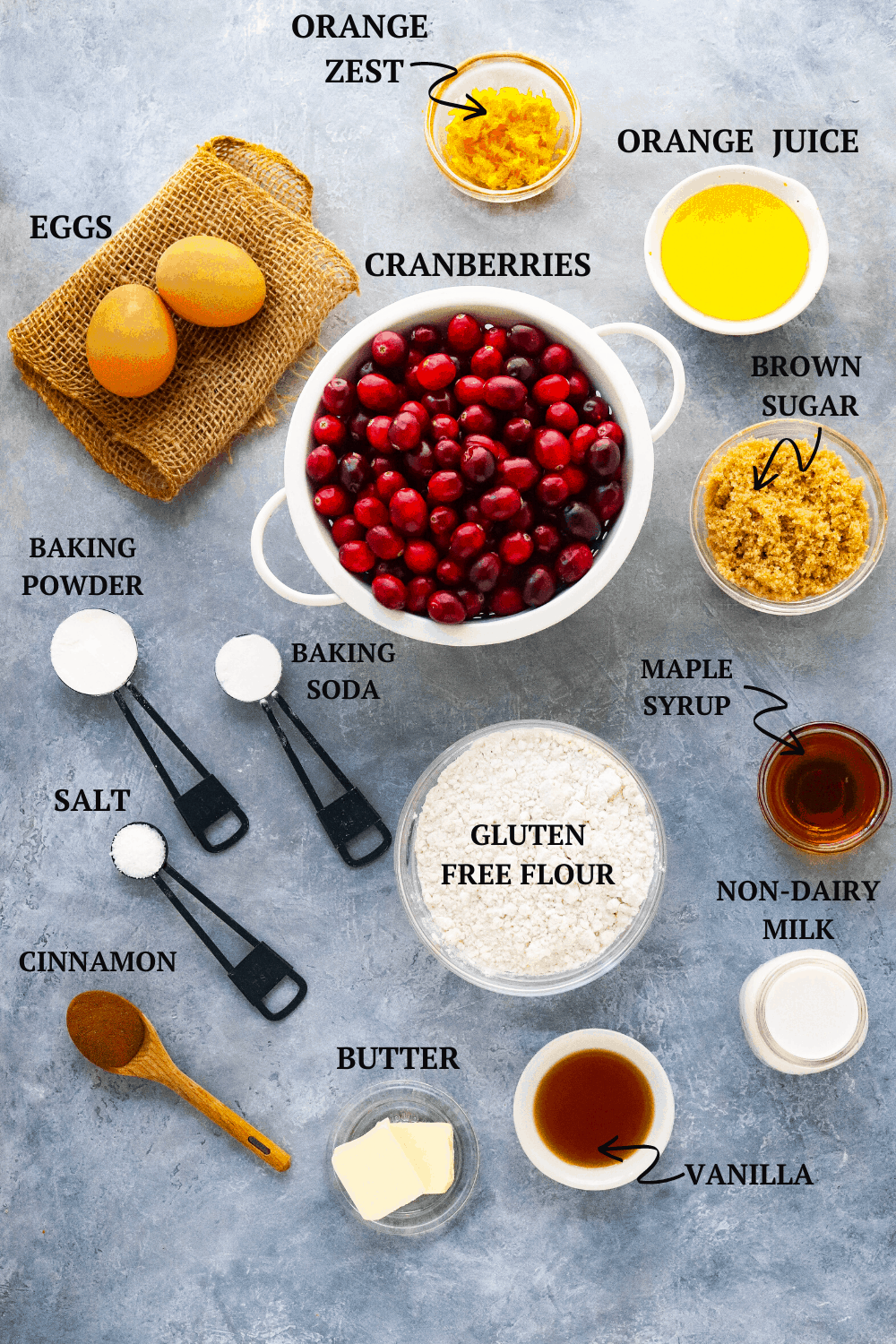 cranberries, eggs, flour, and other baking ingredients in bowls on a gray surface.