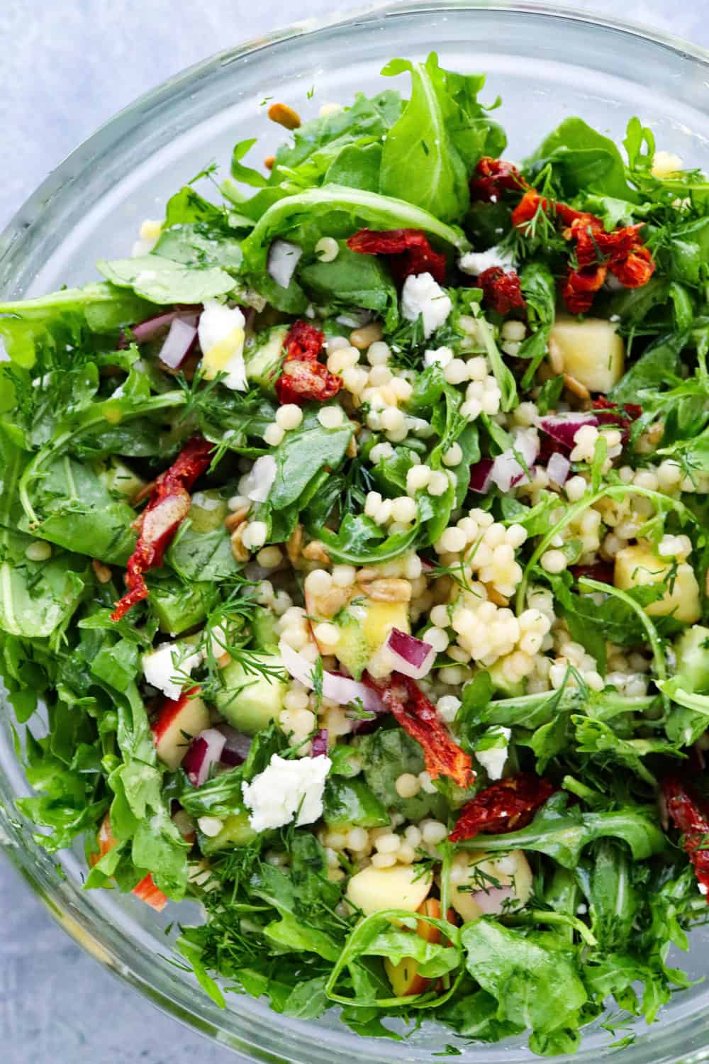 Mixed up couscous salad with arugula and tomatoes on it.