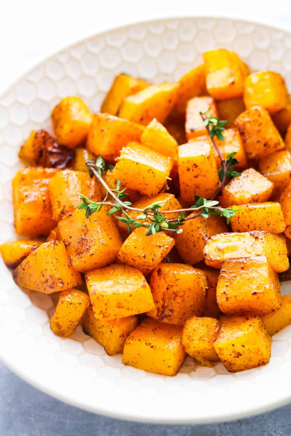 Roasted squash with thyme on top of it in a white bowl.