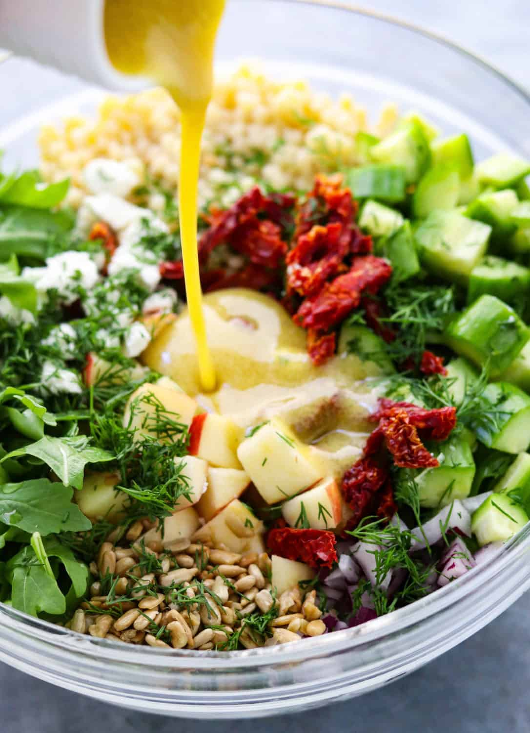 pouring mustard dressing into a bowl filled with Israeli couscous salad