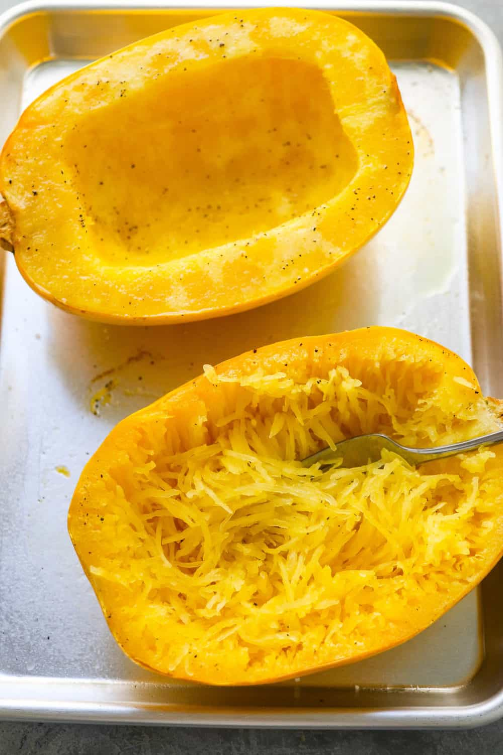 two halves of spaghetti squash on a baking sheet with a fork in one of them