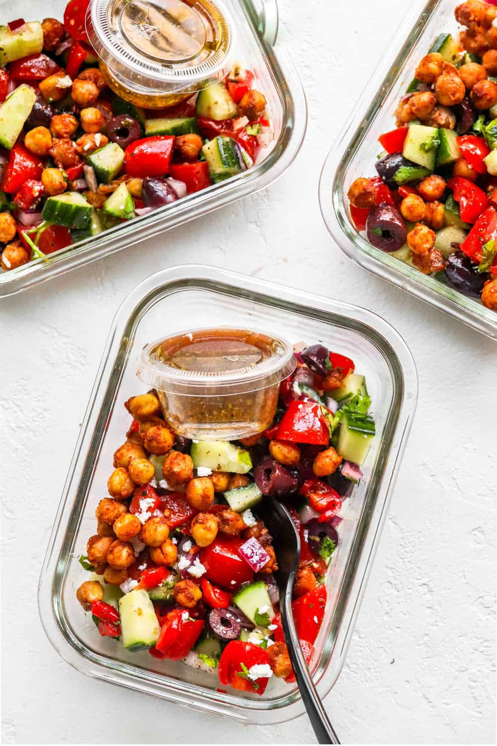 3 glass containers filled with mediterranean chickpea salad with a salad dressing container in each and a fork in one of the containers