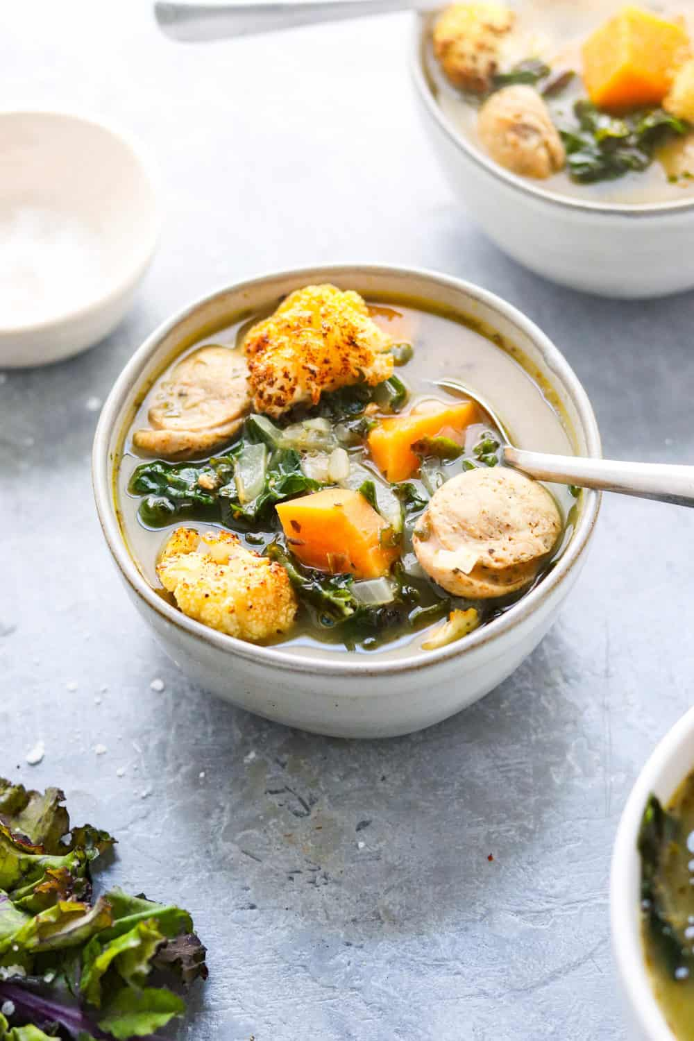 round gray bowl filled with soup topped with sausage and green and orange veggies with a spoon in the bowl of soup.