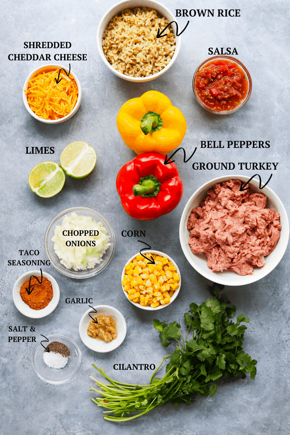 rice, peppers, cheese, salsa, limes, ground turkey and spices on a gray board