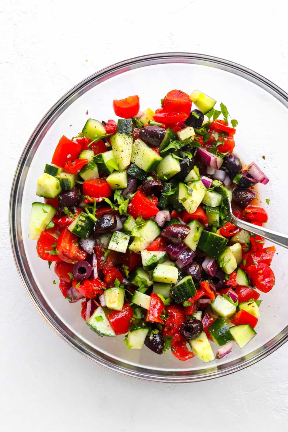 round glass bowl filled with chopped cucumber, tomatoes, olives and onion with a spoon in it