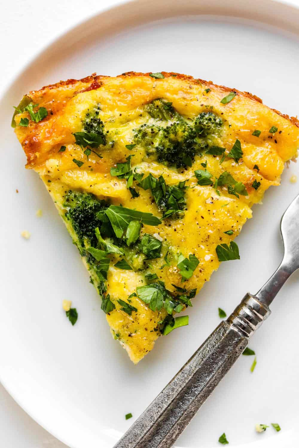 Slice of broccoli quiche on a white plate with a fork next to it.