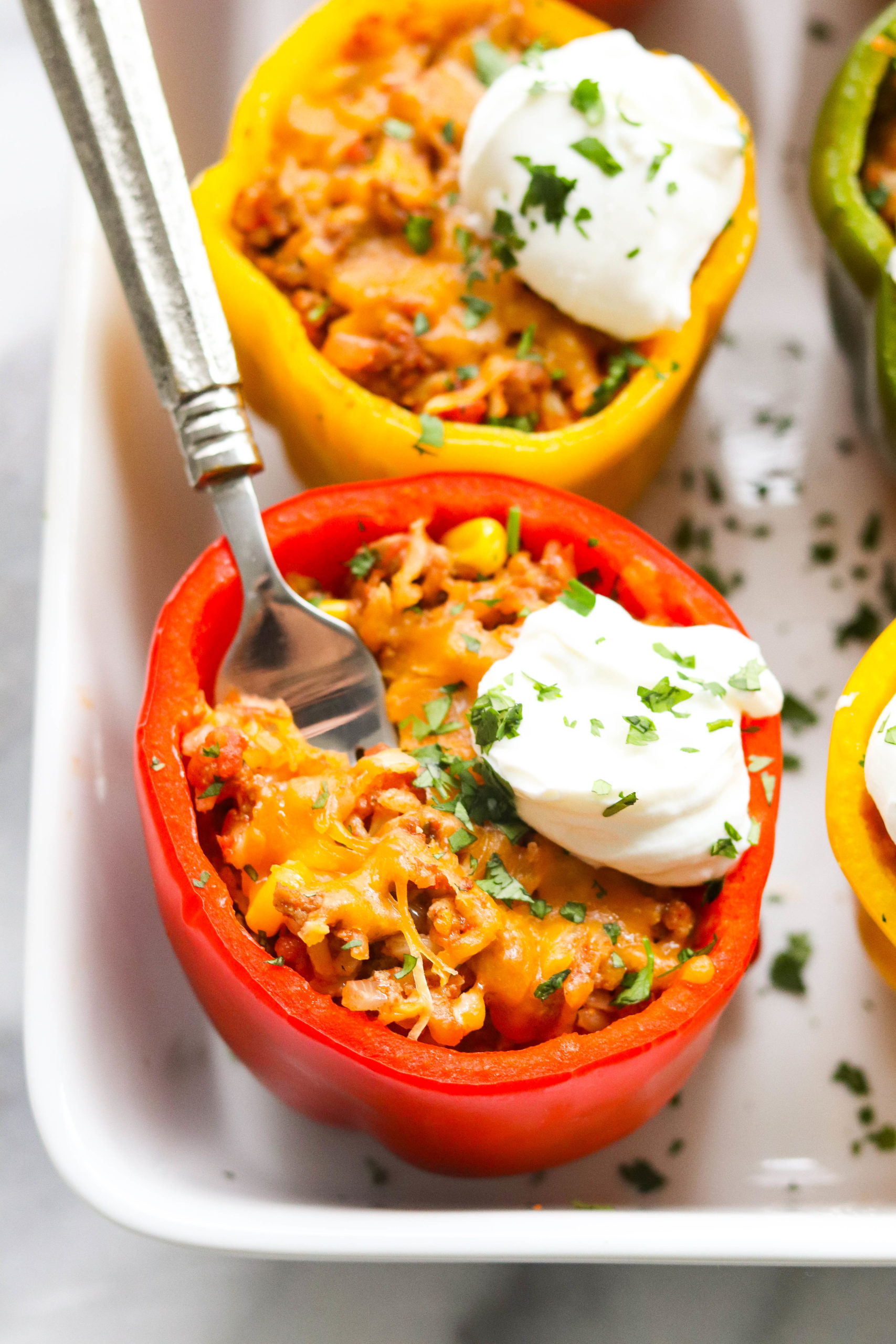 pan of taco stuffed bell peppers with sour cream and herbs on top