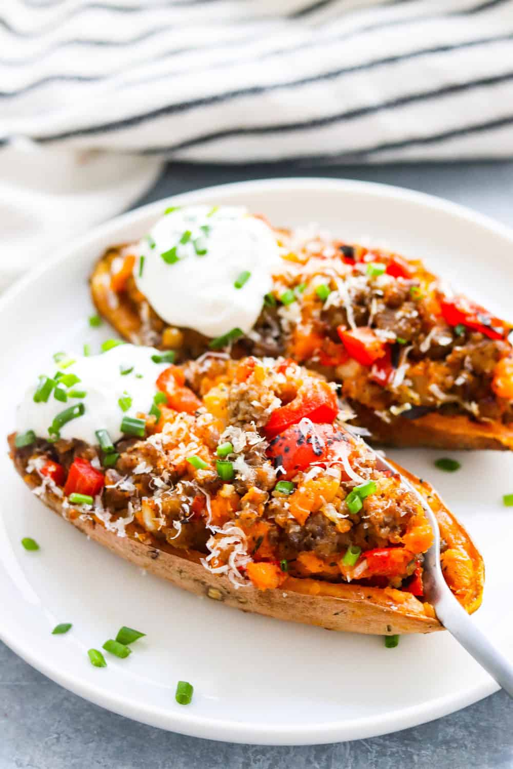 2 sausage stuffed sweet potatoes on a round white plate topped with sour cream and chives