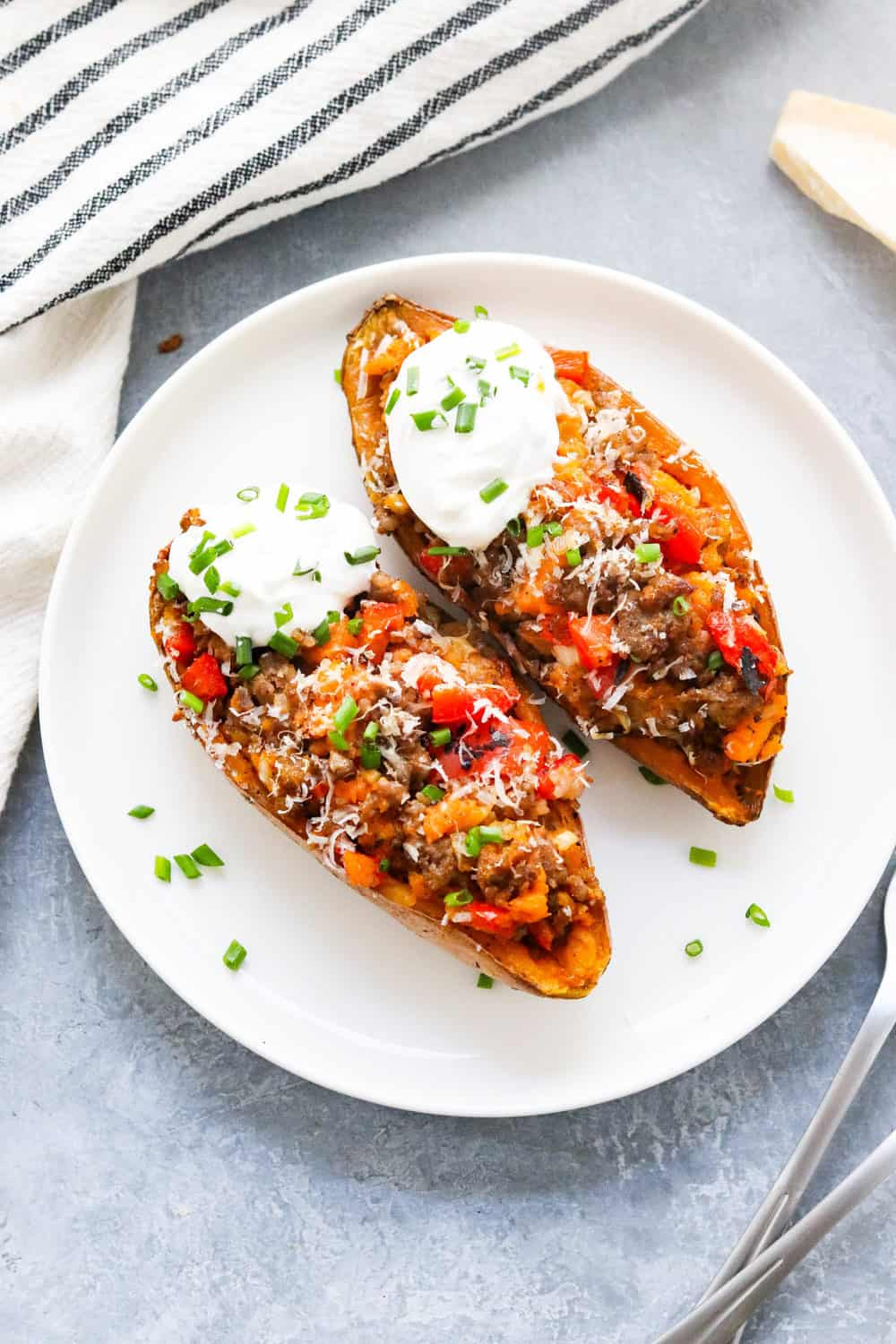 sausage loaded baked sweet potatoes on a plate with sour cream on them