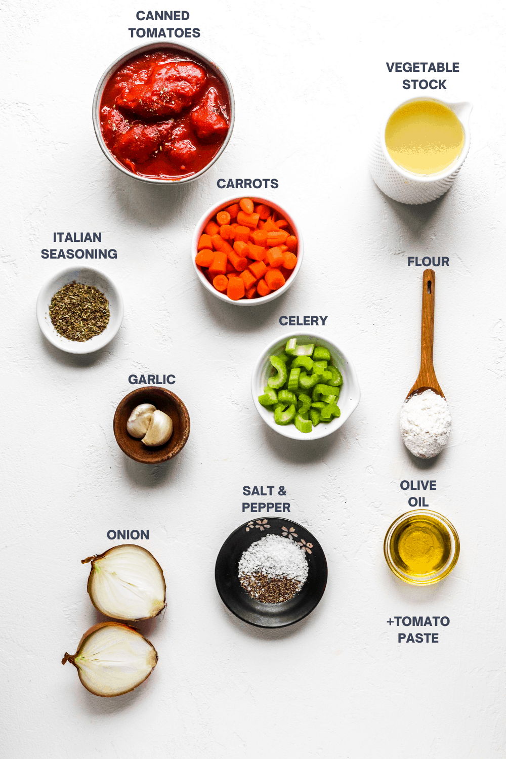 bowls filled with ingredients for tomato soup on a white surface