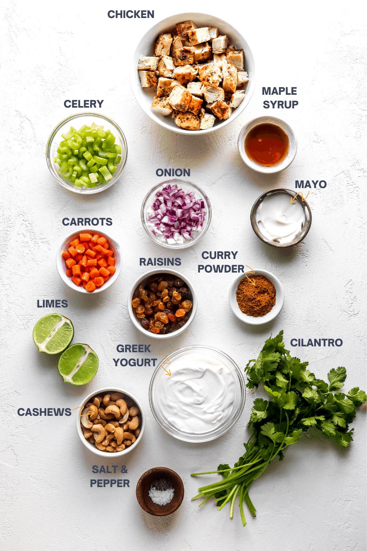 chicken, veggies, yogurt and cilantro in bowls on a white surface