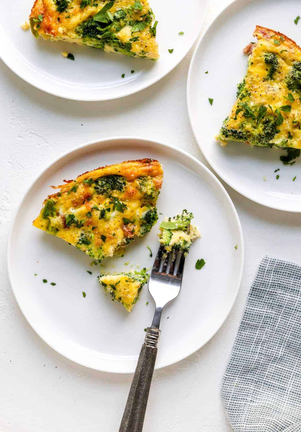 healthy breakfast quiche with greens cut in a slice on a white round plate with more behind it