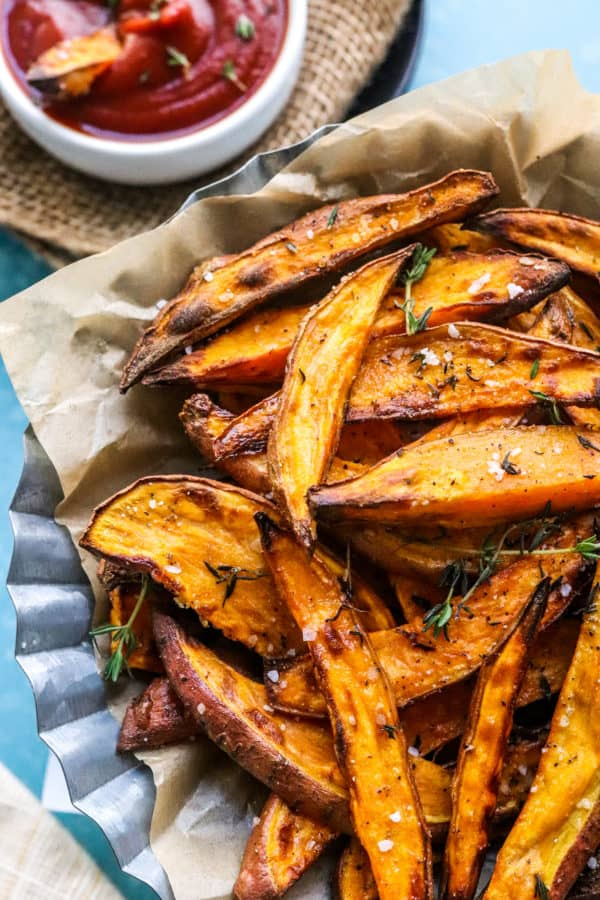 Golden brown sweet potato wedges in a basket on top of brown paper