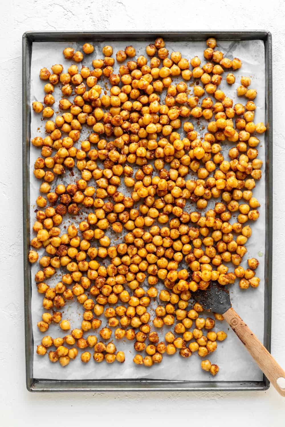 Baking sheet covered with white parchment paper, topped with a pile of chickpeas and a gray spatula on it