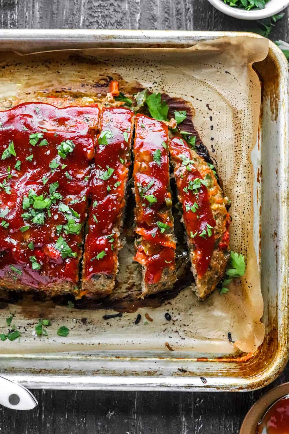 sliced meatloaf onto of parchment paper on. baking sheet.