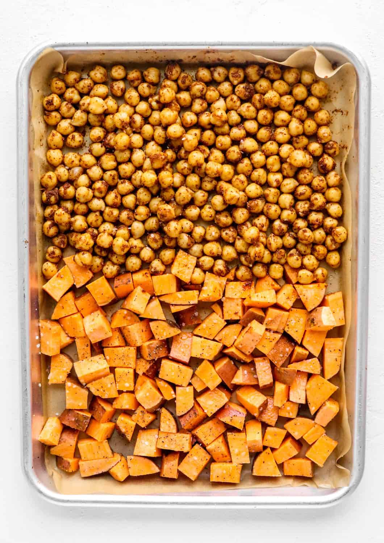 Seasoned chickpeas and diced sweet potato on a baking sheet