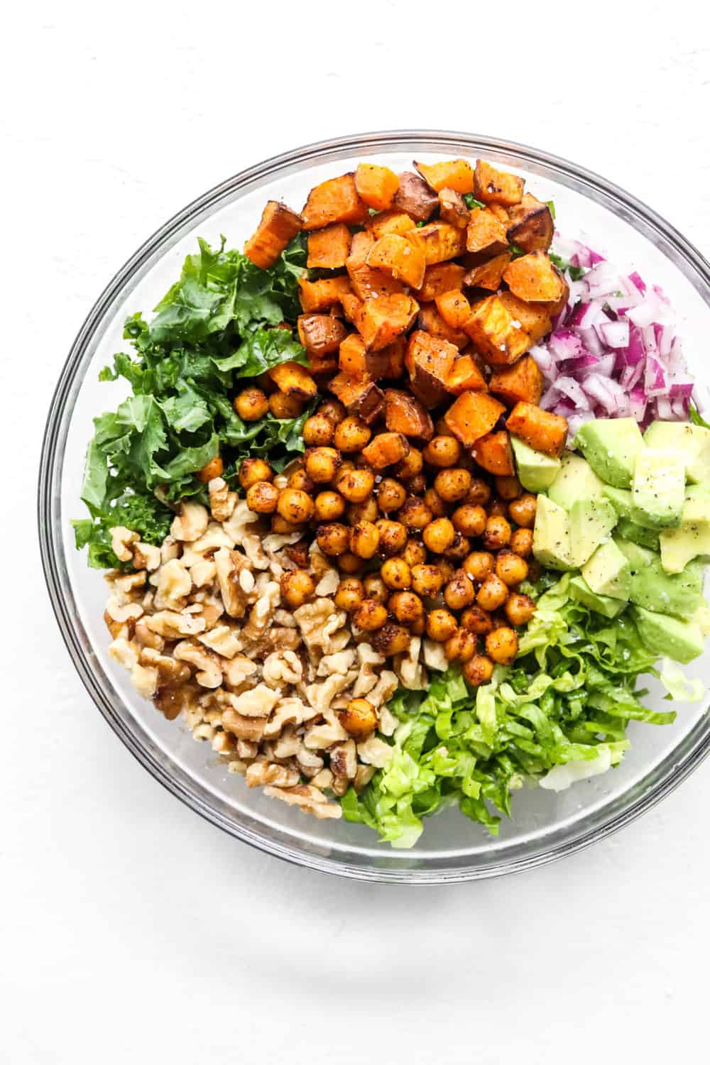 chopped kale, romaine lettuce, roasted sweet potatoes, diced onion and walnuts in a round glass bowl