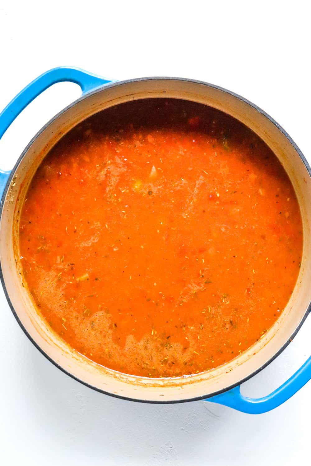 large blue pot filled with tomato soup