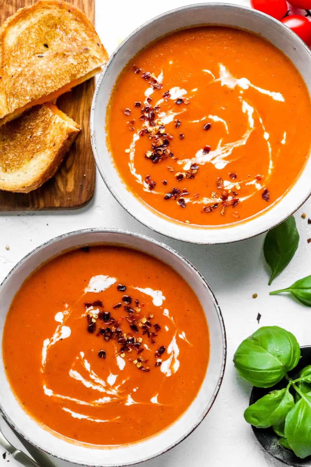 2 soup bowls with tomato soup in them and a grilled cheese next to it with basil near it