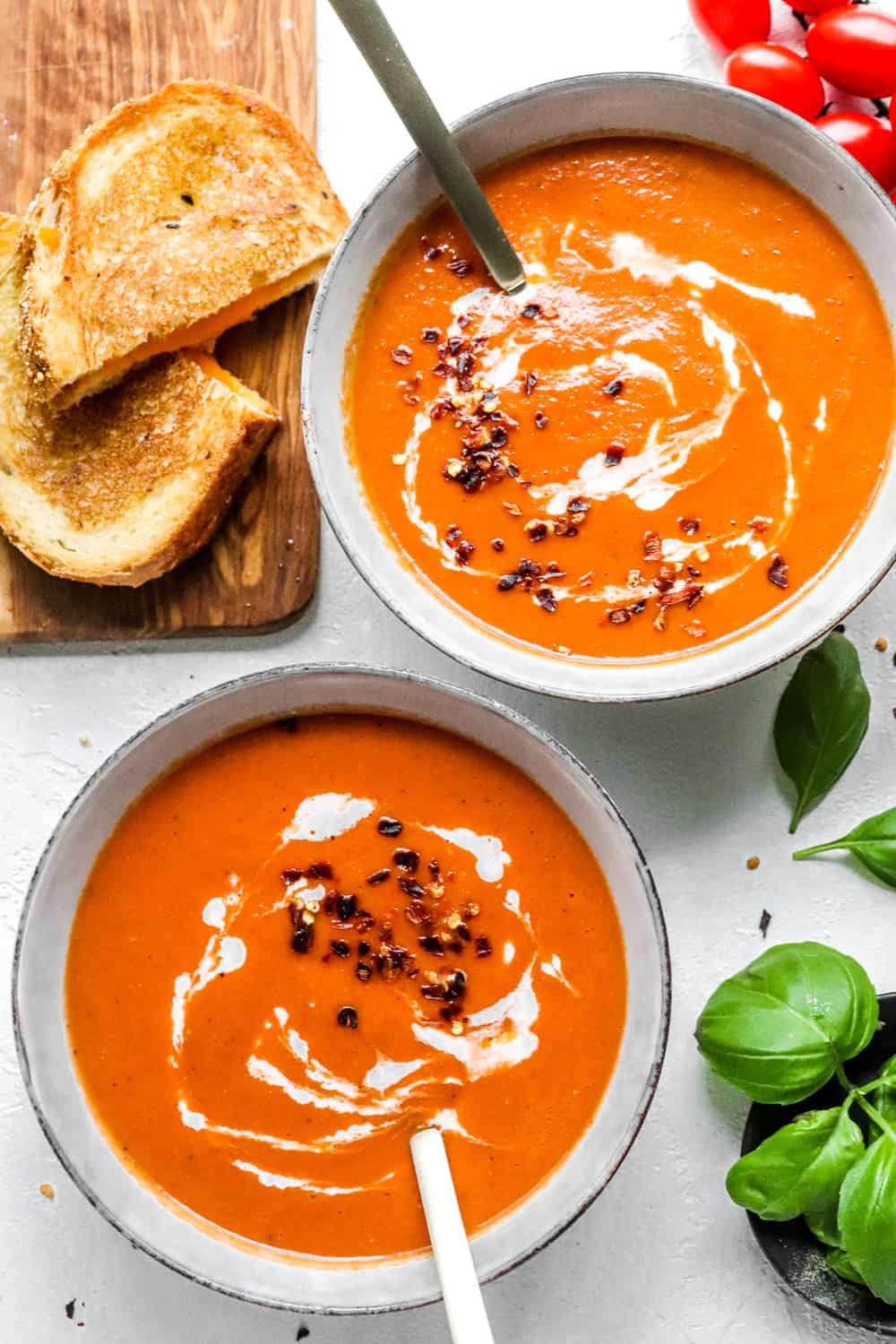 two bowls filled with creamy tomato soup topped with cream with a spoon in each bowl
