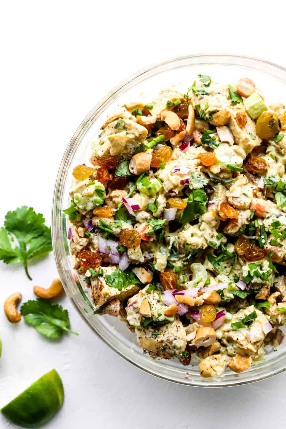 Bowl of gluten free curry chicken salad with purple onion and cilantro in it and limes and cashews next to it.