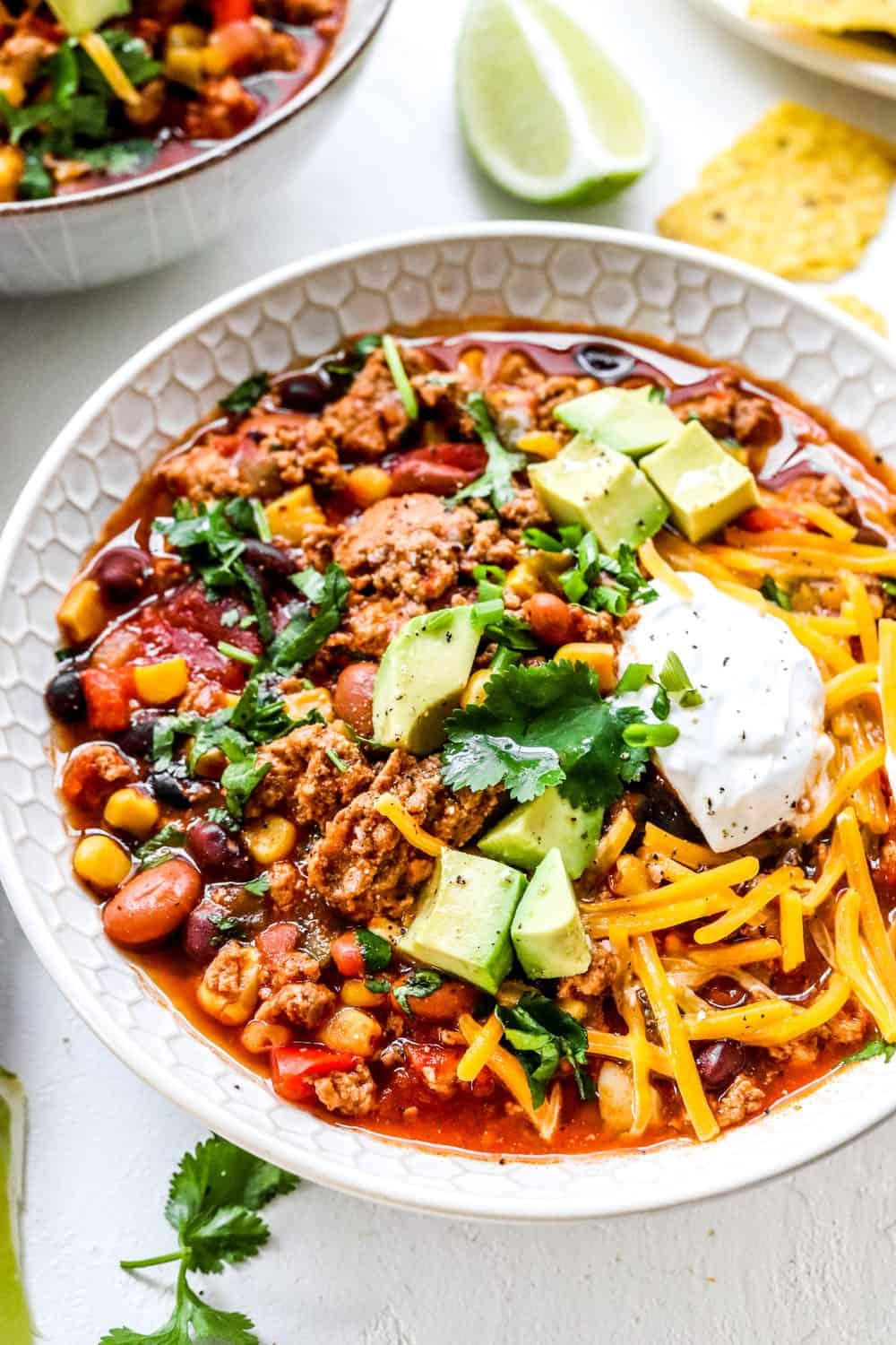 Turkey chili in a round white bowl with avocado and cheese on top of it
