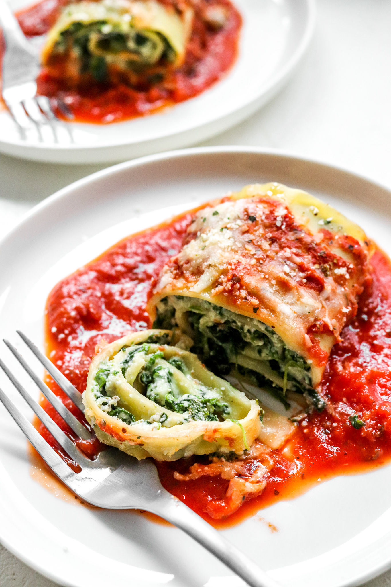 Lasagna roll filled with cheese and spinach covered in red sauce with a pice cut on a plate with a fork next to it.