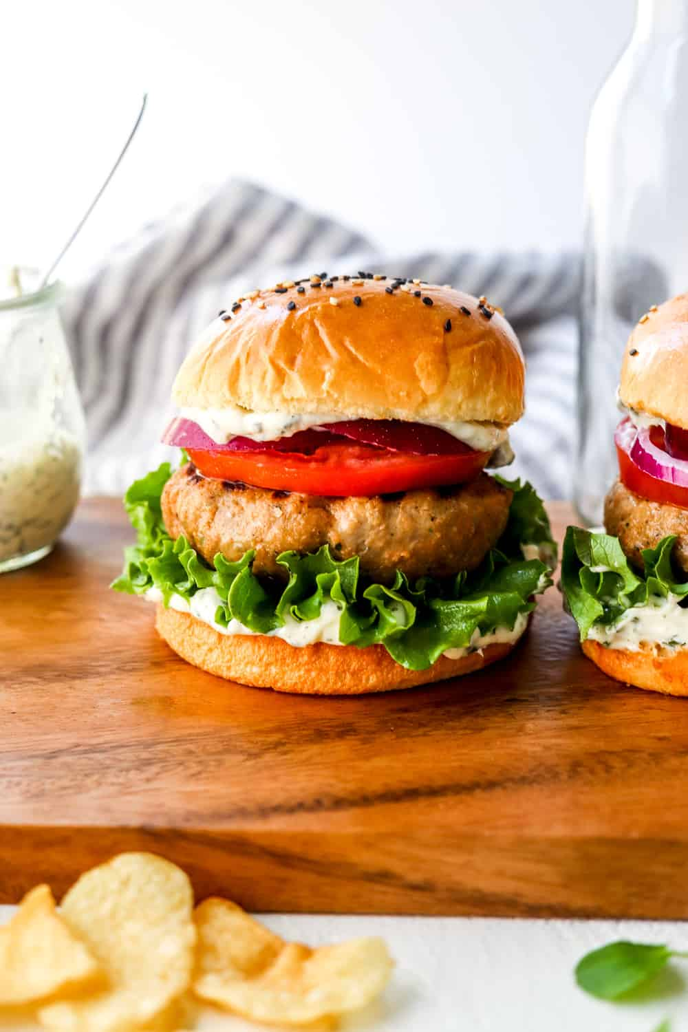 Burger made with turkey between a bun with mayo, lettuce and tomato on a wooden surface with another burger next to it.