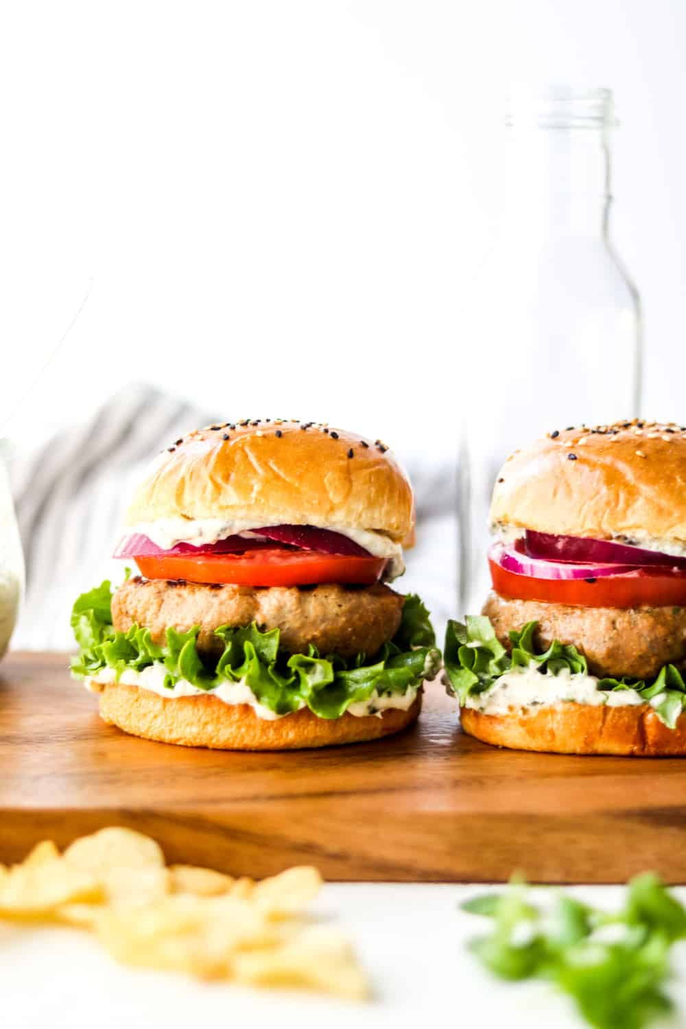 two turkey burgers on buns with sesame seeds on top and lettuce an tomato in them on a wooden board.