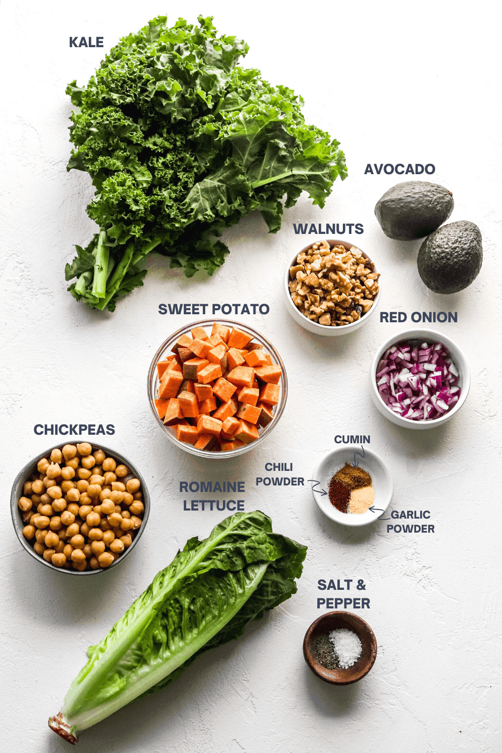 big bunch of kale, avocado, walnuts, diced sweet potato, chickpeas and seasoning on a white surface